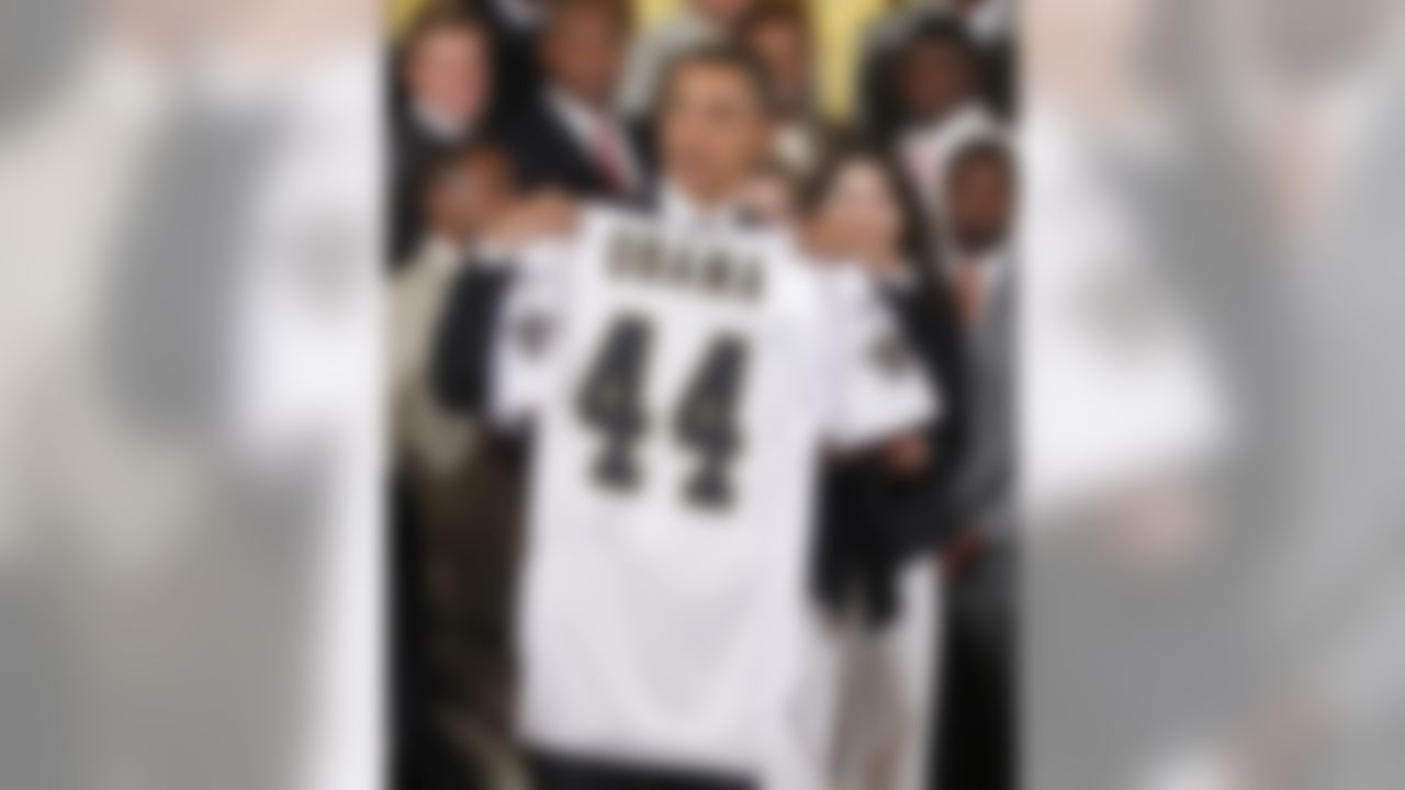 President Barack Obama holds up a personalized New Orleans Saints football team jersey as he stands with the 2009 NFL Super Bowl Football Champions New Orleans Saints, Monday, Aug. 9, 2010, during a ceremony in the East Room of the White House in Washington honoring the team. (AP Photo/Charles Dharapak)
