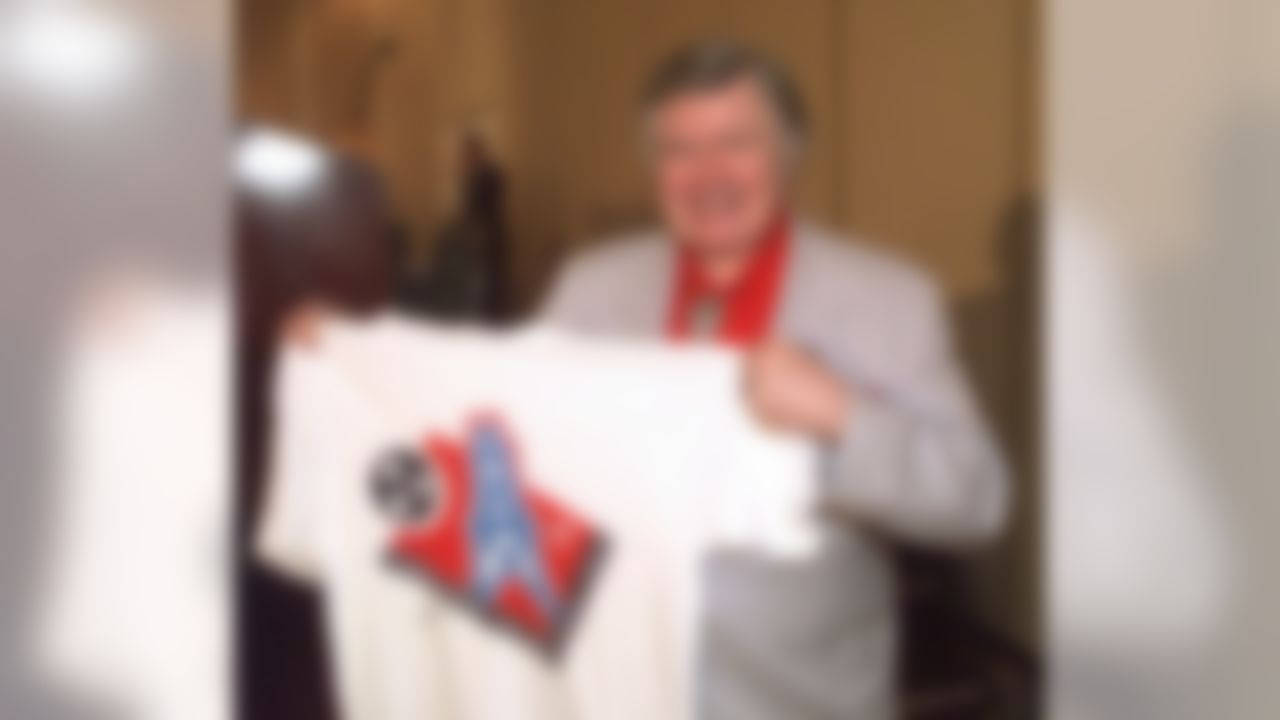 Houston Oilers owner Bud Adams shows off a T-shirt with the new logo the team will use this season when it moves to Tennessee. The logo was unveiled in Nashville on Thursday, June 12, 1997.  (AP Photo/Mark Humphrey)