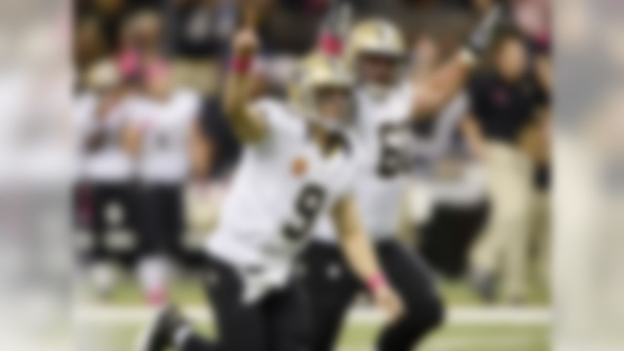 Drew Brees reacts with center Brian De La Puente (60) after throwing a touchdown pass in the first half of an NFL football game at the Mercedes-Benz Superdome in New Orleans, Sunday, Oct. 7, 2012. The touchdown pass was in his 48th consecutive game, breaking Johnny Unitas' NFL record which stood for over 50 years, during an NFL football game against the San Diego Chargers. (AP Photo/Bill Feig)