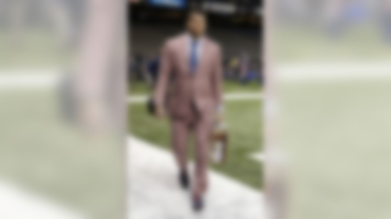 """Tennessee Titans tackle Taylor Lewan's pregame ensemble is all about """"pop,"""" with a square-patterned salmon-colored tailored suit, blue polka-dot tie, light blue shirt and navy oxfords with red laces.  The look comes together with a gold watch and a vintage travel suitcase that showcases all the places he's been. If he's not the Most Interesting Man in the World, he's at least one of most interestingly dressed."""