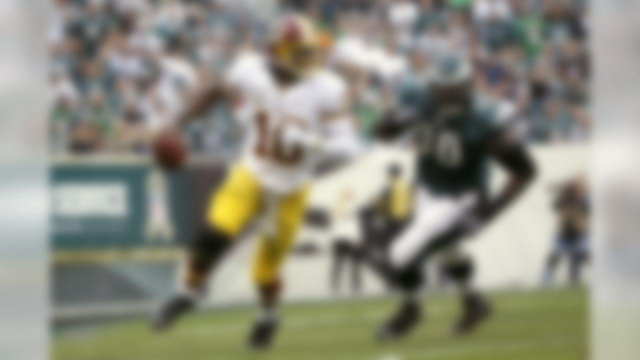Washington Redskins quarterback Robert Griffin III, left, scrambles past Philadelphia Eagles nose tackle Bennie Logan during the first half of an NFL football game in Philadelphia, Sunday, Nov. 17, 2013. (AP Photo/Matt Slocum)