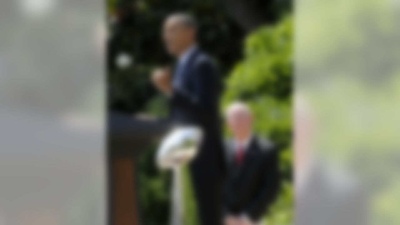 With the Super Bowl trophy in the foreground, and New York football Giants head coach Tom Coughlin in the background,  President Barack Obama speaks on the South Lawn at the White House in Washington, Friday, June 8, 2012, during a ceremony honoring the Super Bowl XLVI Champions. (AP Photo/Susan Walsh)