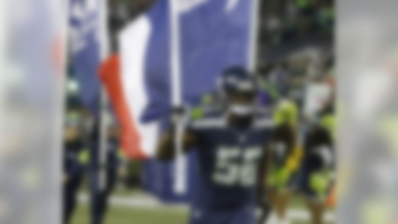Seattle Seahawks defensive end Cliff Avril runs out of the tunnel carrying a French flag in support of France, which was hit with terrorist attacks in Paris on Friday, before an NFL football game against the Arizona Cardinals, Sunday, Nov. 15, 2015, in Seattle. (AP Photo/Elaine Thompson)
