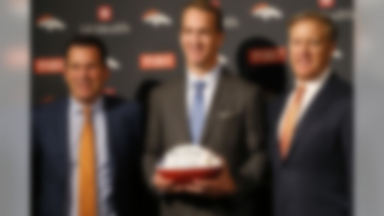 Denver Broncos quarterback Peyton Manning, center, joins head coach Gary Kubiak, left, and team general manager John Elway after Manning's retirement announcement at team headquarters Monday, March 7, 2016, in Englewood, Colo. Manning, who has been in the NFL for the past 18 years, is retiring after winning five MVP trophies and two Super Bowl championships, the most recent last month against the Carolina Panthers. (AP Photo/David Zalubowski)