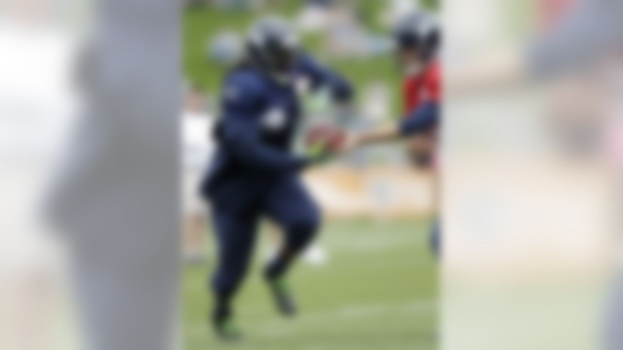 Seattle Seahawks running back Marshawn Lynch takes a handoff from quarterback Matt Flynn during NFL football training camp, Monday, July 30, 2012, in Renton, Wash. (AP Photo/Ted S. Warren)