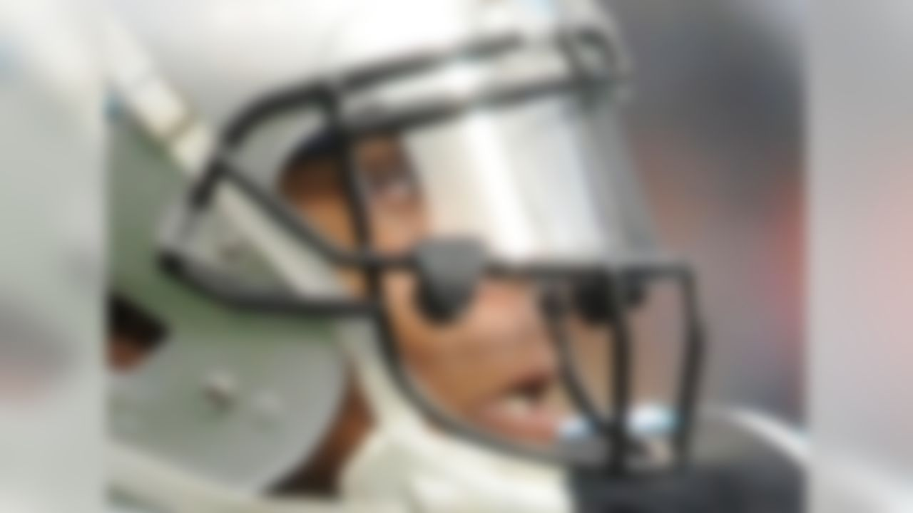 1) Who is this NFL player who took the league by storm in 2011, passing for more than 4,000 yards in his rookie season?