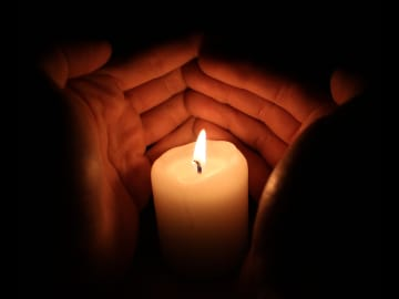 Hands covering a candle