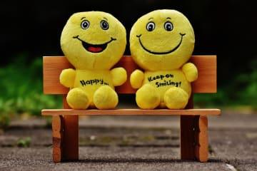 Two yellow plush toys smiling