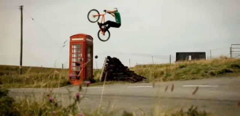 Une photo du trialiste Danny MacAskill faisant un saut au dessus d'une cabine téléphonique