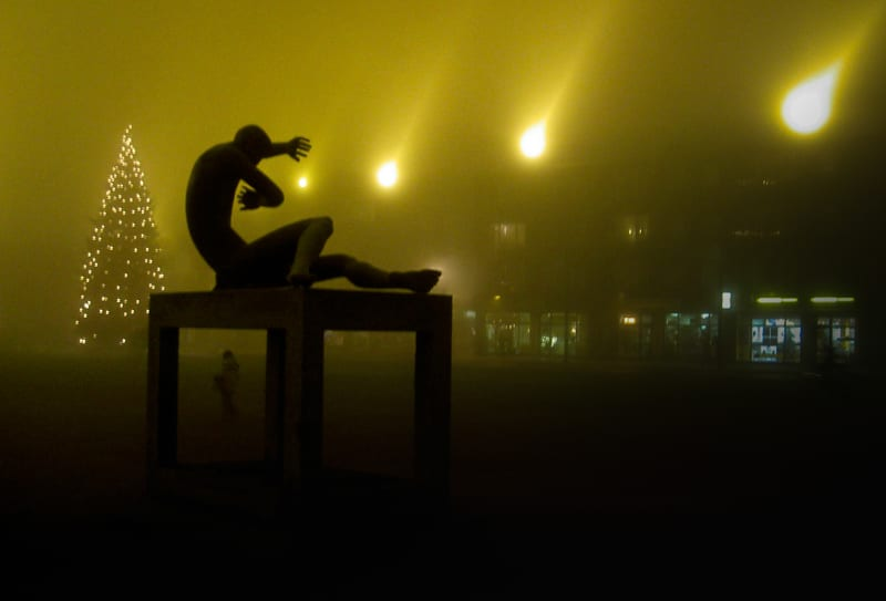 A photo of a statue in the fog, at night