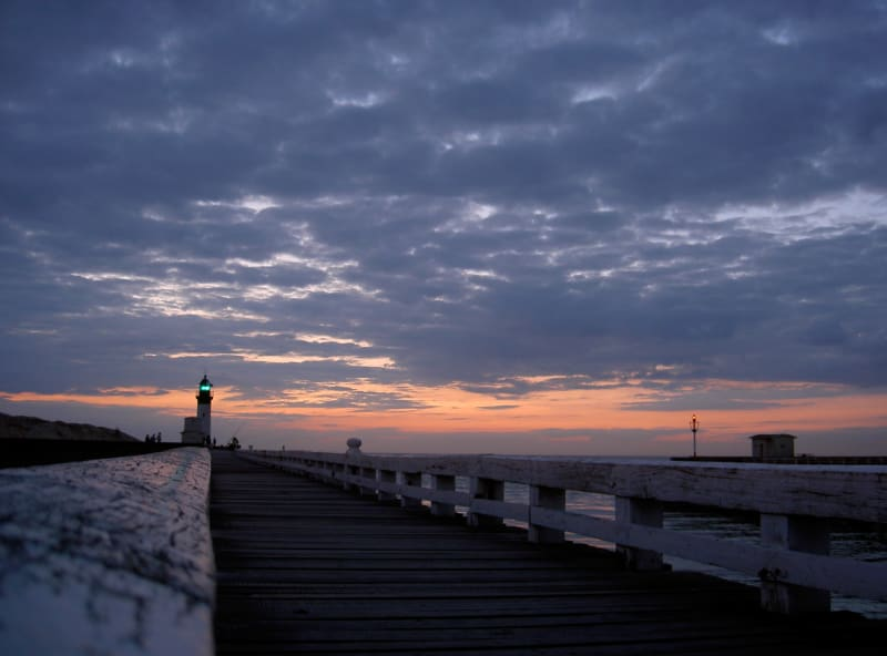 A photo of a pier and lighthouse in sunset