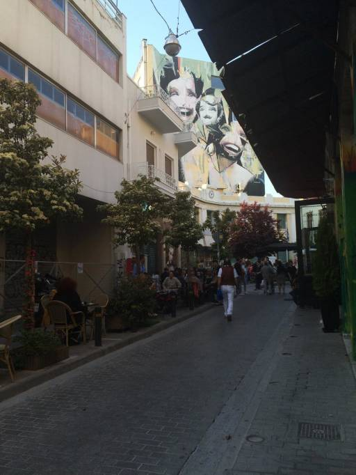 A street with a giant mural in the background