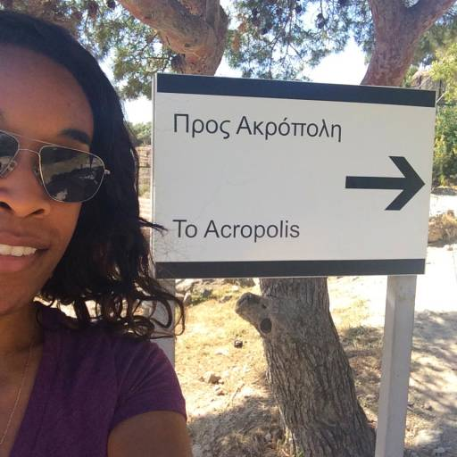 Me standing next to a sign that says TO ACROPOLIS