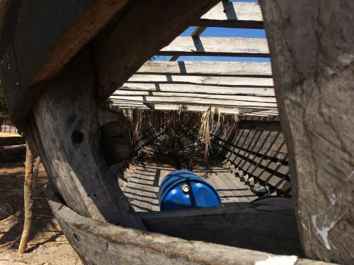 Interio of the boat from a gaping hole in its side, with the clear sky visible through the slats