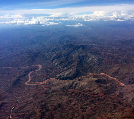 Aerial view of mountains with a ruddy river flowing through