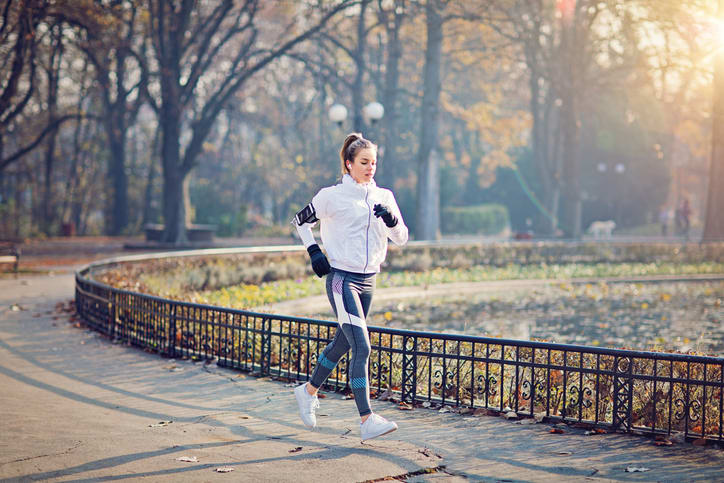 Woman going for a run in the park wearing gloves and listening to music