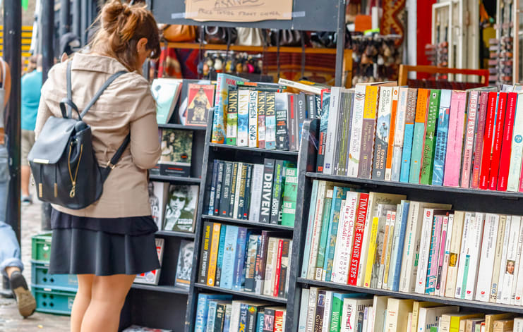 London, UK - September 1, 2017 - Shelves of used books on display at a second hand book shop in Camden Market with a female customer browsing in the background