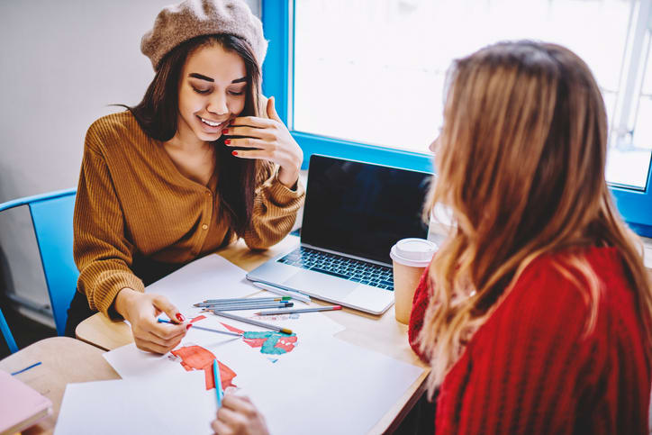 Smiling african female student designer in trendy apparel drawing sketches for university exam sitting at desktop with woman friend, modern laptop computer with mock up screen staying at table