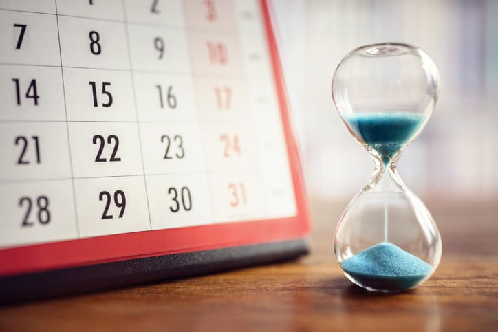 Hourglass with blue sand in front of red calendar