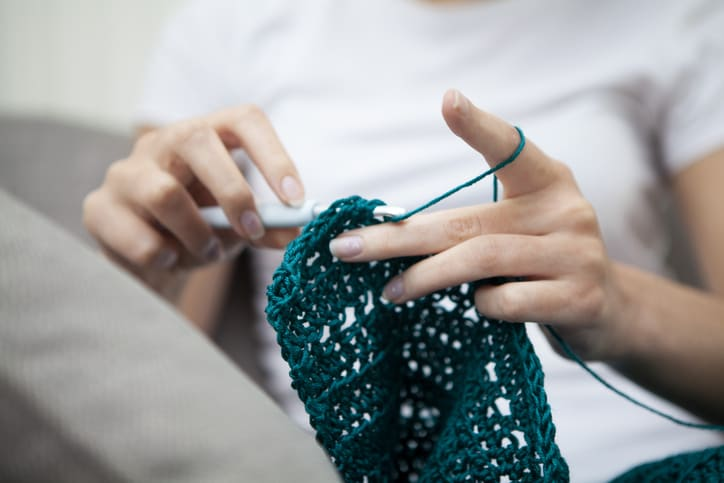 Low angle view of a teenager doing crochet with selective focus on the hands