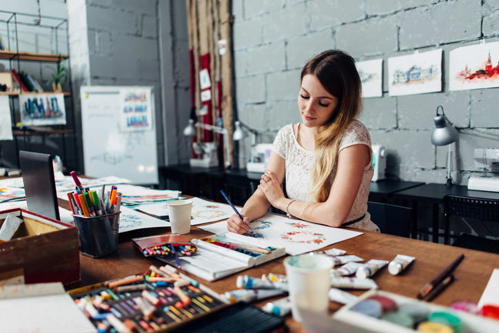 Focused young female artist drawing sketches using colored pencils sitting at her stylish workshop.