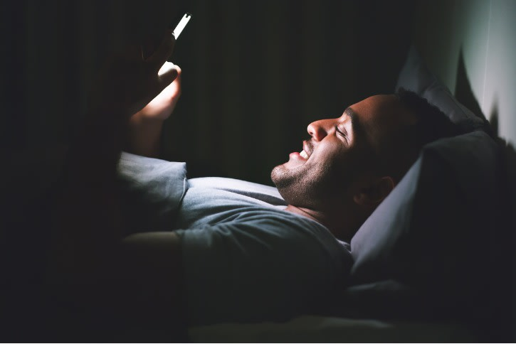 man on his phone in bed