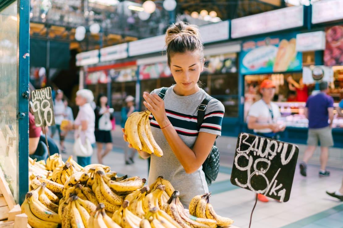 Woman Buying Bananas at Market