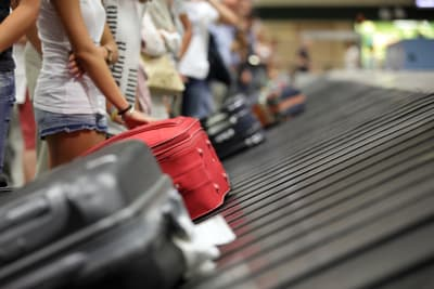picture showing holidaymakers waiting for bags at a luggage carousel