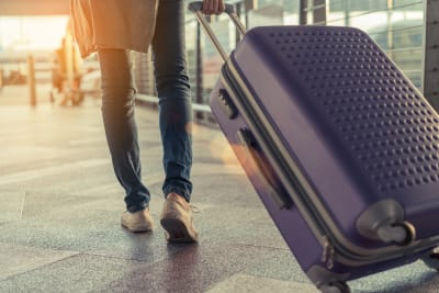 picture showing woman dragging suitcase through airport, going on holiday