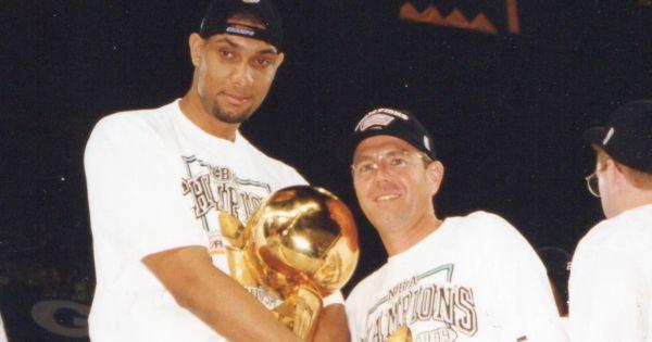 Image of Dr. David Schmidt with Tim Duncan holding 1999 NBA Championship trophy