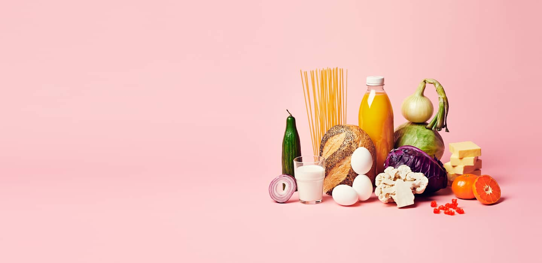 Klynge med dagligvarer som juice, pasta og løk på rosa bakgrunn
