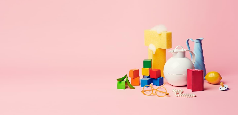 Klynge med forskjellige objekter som klosser, kanne og svamper på rosa bakgrunn