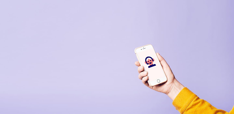 Hånd som holder en telefon på lilla bakgrunn