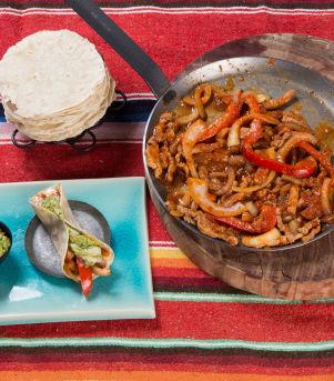 Fajitas med smeltet cheddarsaus, paprika og løk