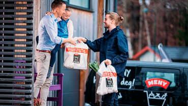Ansatt i MENY som leverer varer fra MENY nettbutikk på døren til kunde