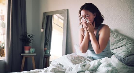 Jente som sitter i seng med en dyne rundt seg og snyter nesa