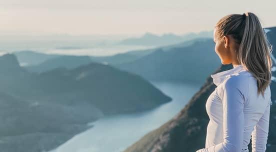 Foto av en sprek jente med norsk fjord i bakgrunnen
