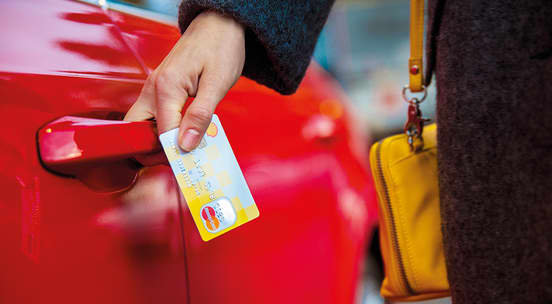 Hånd som holder i Shell MasterCard mens den åpner en rød bildør