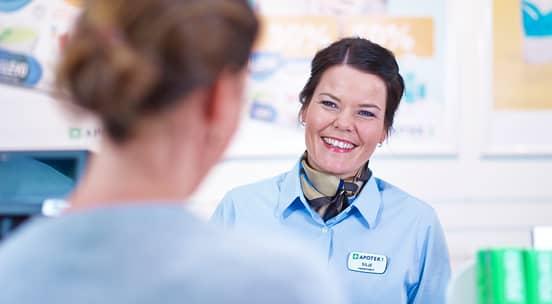 Ansatt som smiler imøtekommende til en kunde