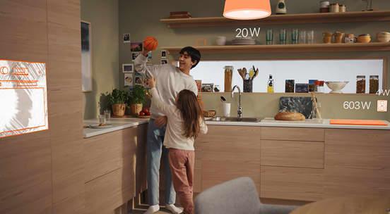 Foto av far som smiler til datter på kjøkkenet med en illustrasjon av en fiktiv lampe, stikkontakt og stekeovn på kjøkkenet
