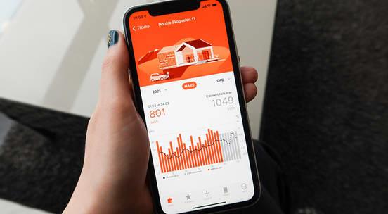 Kvinnehånd som holder en telefon i hånden med Fjordkraft-appen åpen
