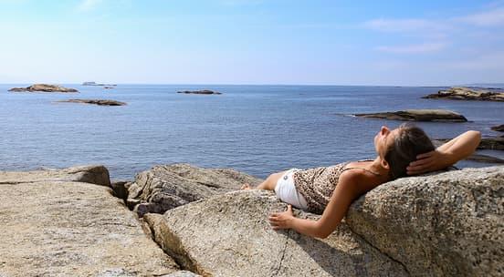Foto av en ung jente som ligger på et svaberg og steker i solen