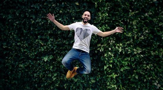 Mann i hvit t-skjorte og Jeans som hopper mens han ler