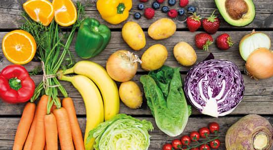 Bord som bugner av fersk frukt og friske grønnsaker