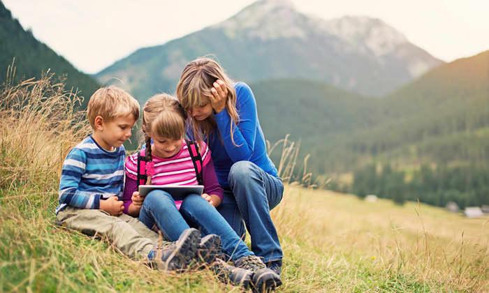 Familie som sitter i gresset med et nettbrett mellom seg