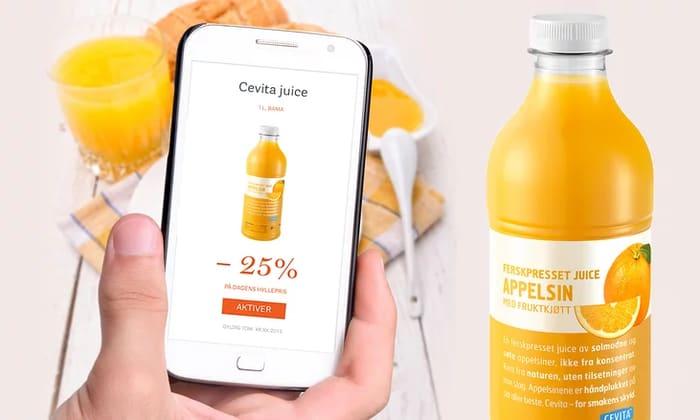 Hånd som holder en mobiltelefon med bilde av en kupong med appelsinjuice