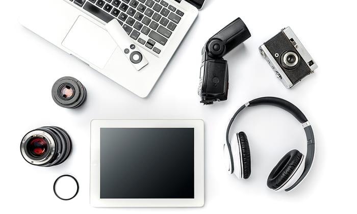 Elektronikkprodukter som nettbrett, PC og høretelefoner som ligger på et bord