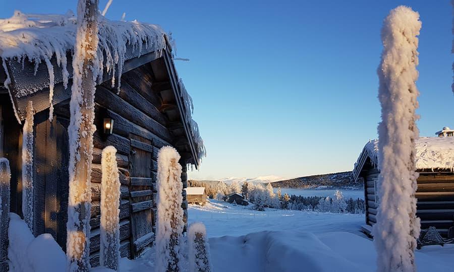 hytte badet i snø og sol