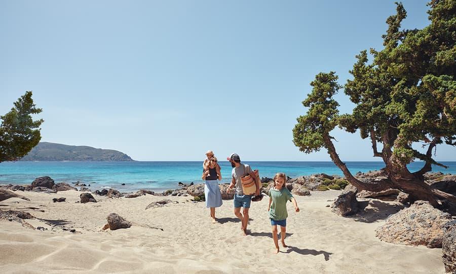 Familie som løper på stranden og ler