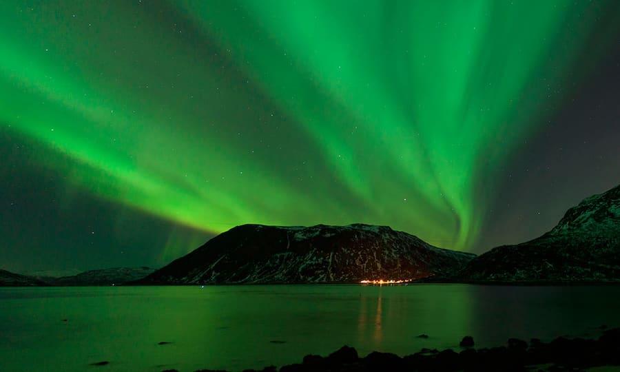 Tromsø badet i grønt nordlys i nattemørket